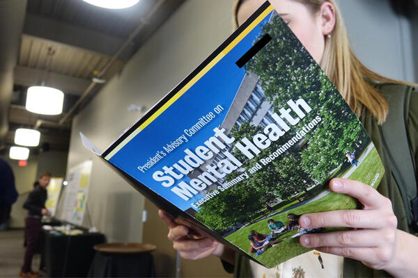 Student holding a Student mental health handbook