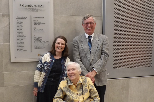 Murray and Nancy stand behind Eileen, who is sitting in a wheelchair