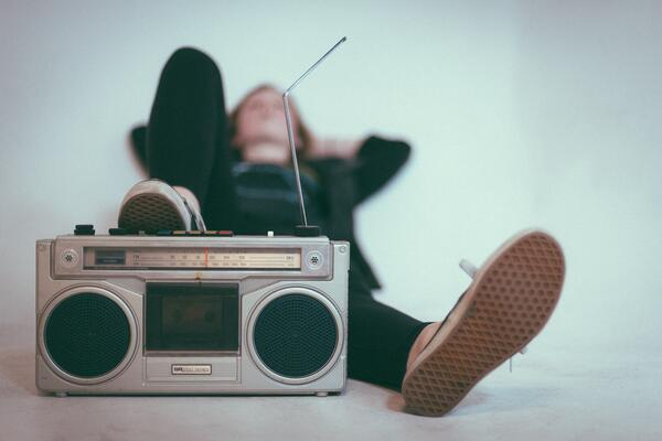Male person listening to music with his feet against a boombox