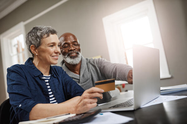 A senior couple using a credit card and laptop while working on their finances at home.