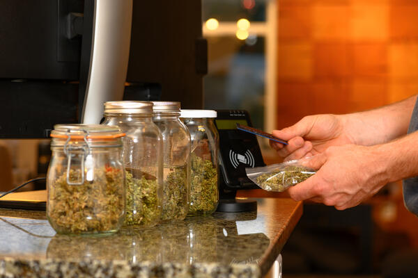 Someone paying by credit card for marijuana at a cannabis dispensary