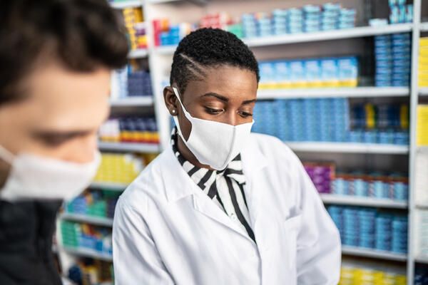 A female pharmacist explaining something to a male customer
