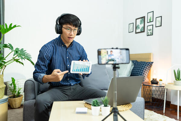 Asian man in headphones writing notes in notebook