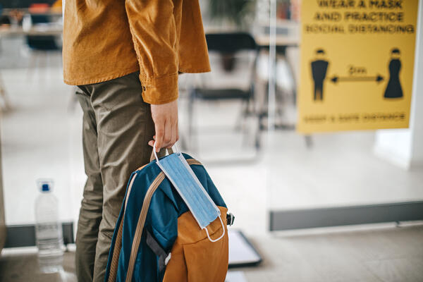 A person holding a knapsack bag and a face mask