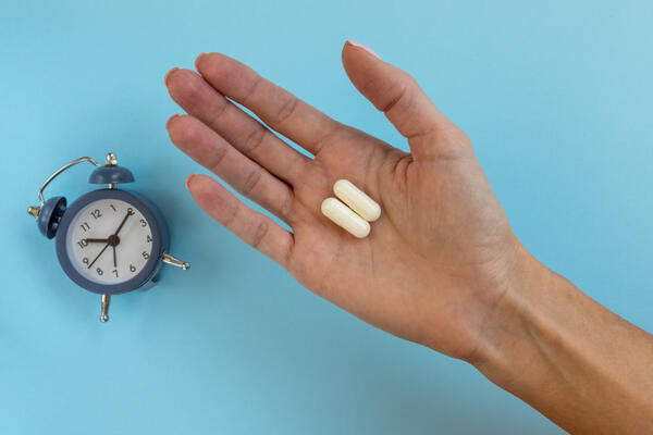 A clock beside a hand with pills