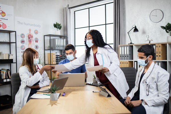 Doctors in protective masks with gadgets co-working at office