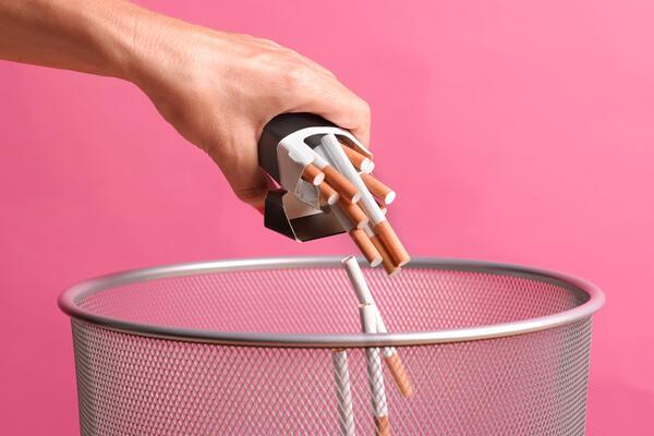 A person's hand dumping cigarettes into a bin