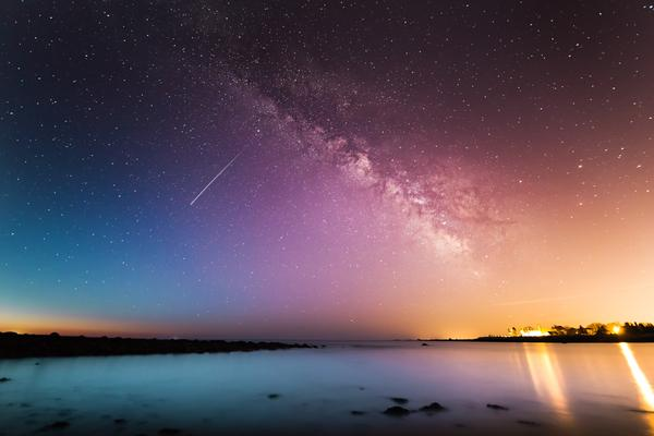 Galaxy seen in evening sky with shooting star