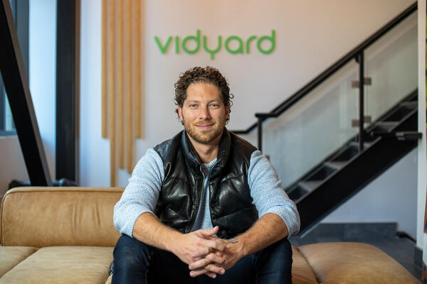 Michael Litt sitting on a couch in front of the Vidyard sign