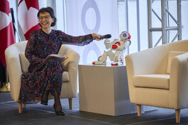 Pearl Sullivan holding a microphone in front of a NAO robot