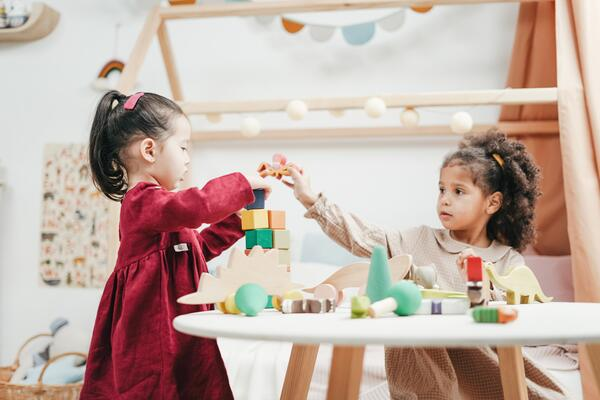 Two girls play with toys in a daycare centre