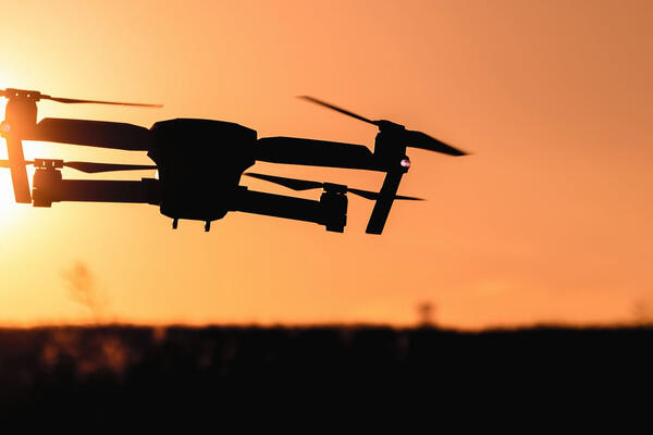 Drone flying towards sunset