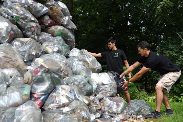 Pickwaste founders next to garbage bags