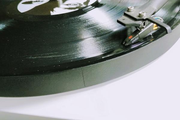 An old-school vinyl album plays on a turntable.