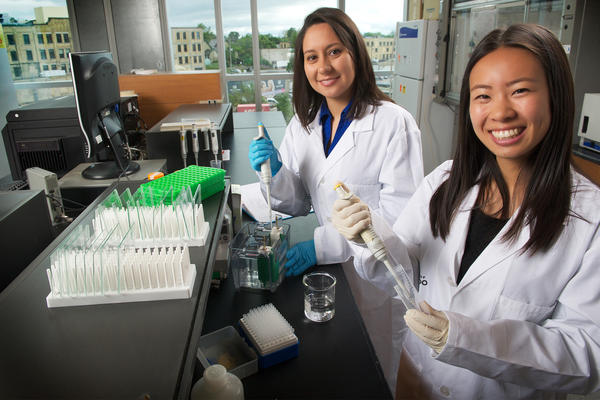 Two female graduate students pipetting in School of Pharmacy lab