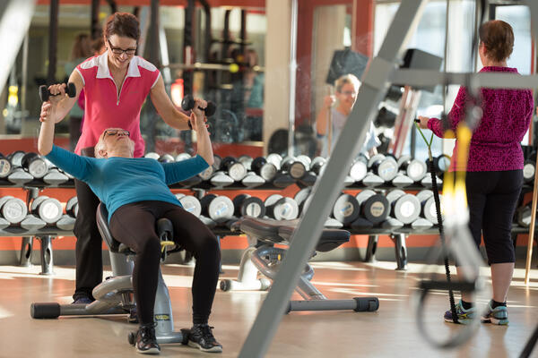Gym setting with woman on bench press, one assisting, and one to the side