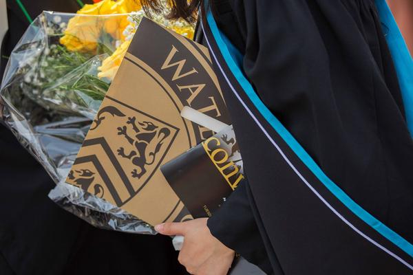 Student holding their diploma and flowers