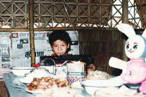 Child at a dinner table in a hut.