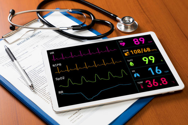 Image of an ipad with heart monitor information on it beside medical tools and clipbaord