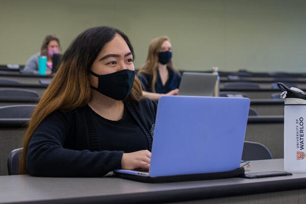 Student sitting at desk with mask