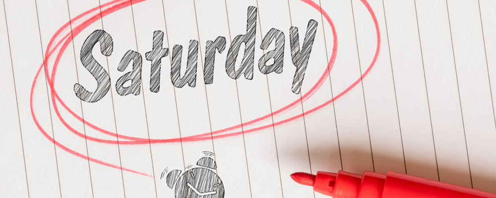 A red marker lies on a note pad next to the word Saturday written in pencil