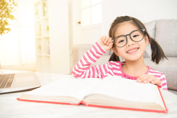Child who is wearing glasses reads a book