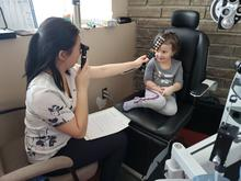 Student volunteer Rachel Ng examines a young patient at the WOVS eye care clinic at Wiikwemikoong First Nation.