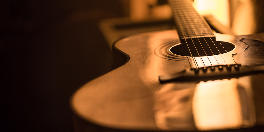light reflecting on the surface of a guitar