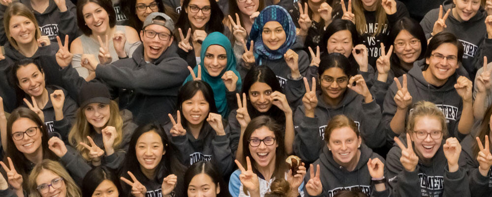 A crowd of Waterloo Optometry students wearing grey hoodies wave at the camera above them