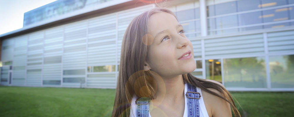 A young girl standing in front of the School looks into the distance