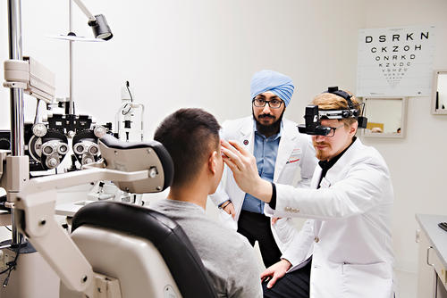 Two male optometry students examine a patient