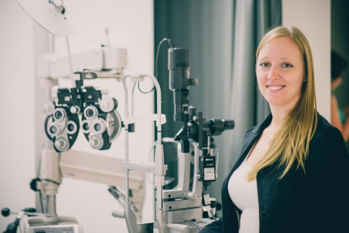 Dr. Kristine Dalton stands beside eye exam equipment in the School of Optometry and Vision Science.
