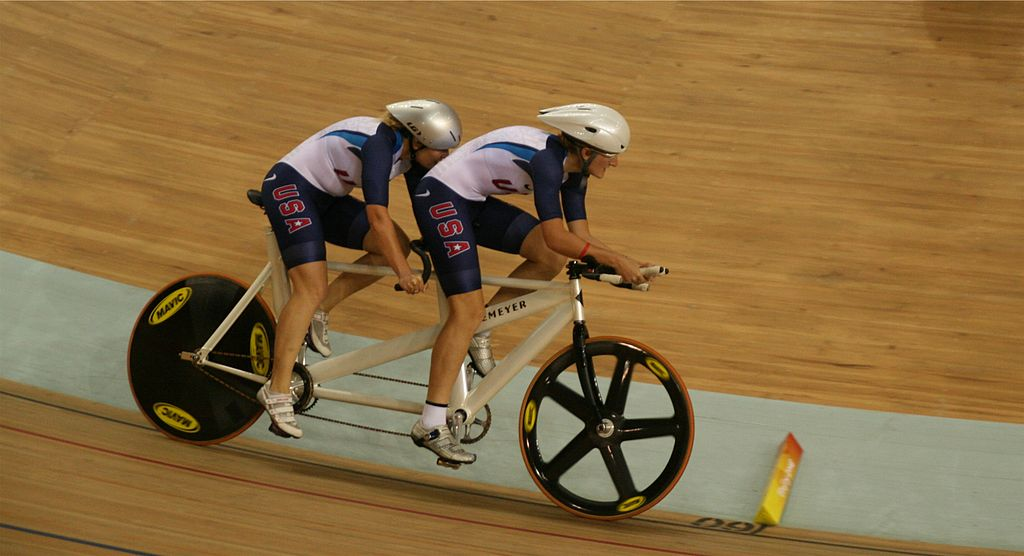 Two cyclists on a tandem bike race on a velodrome track