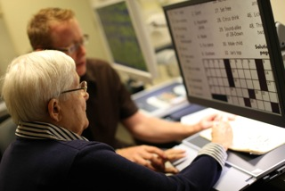 Two people view a crossword puzzle on a CCTV screen