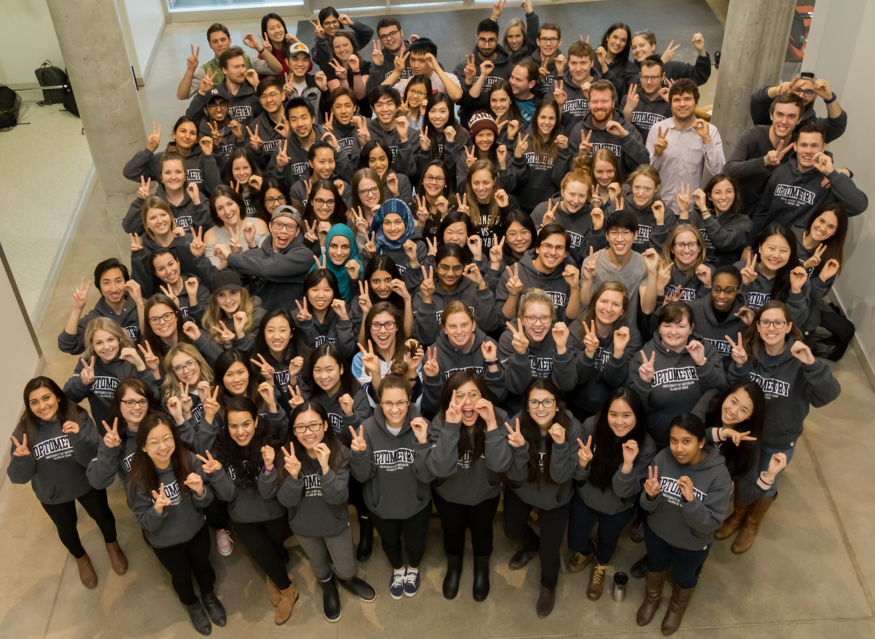 A crowd of Optometry students wearing grey hoodies wave at the camera above them