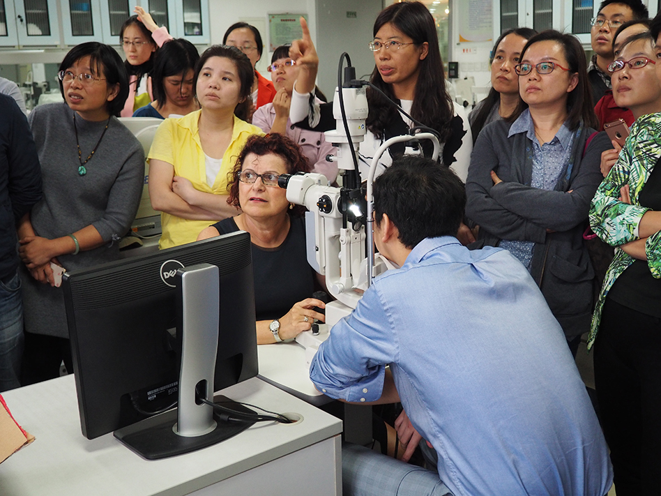 Dr. Gina Sorbara is surrounded by young people as she sits in front of a slit lamp