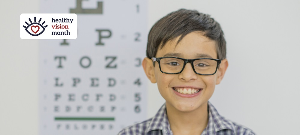 Child wearing new glasses smiles
