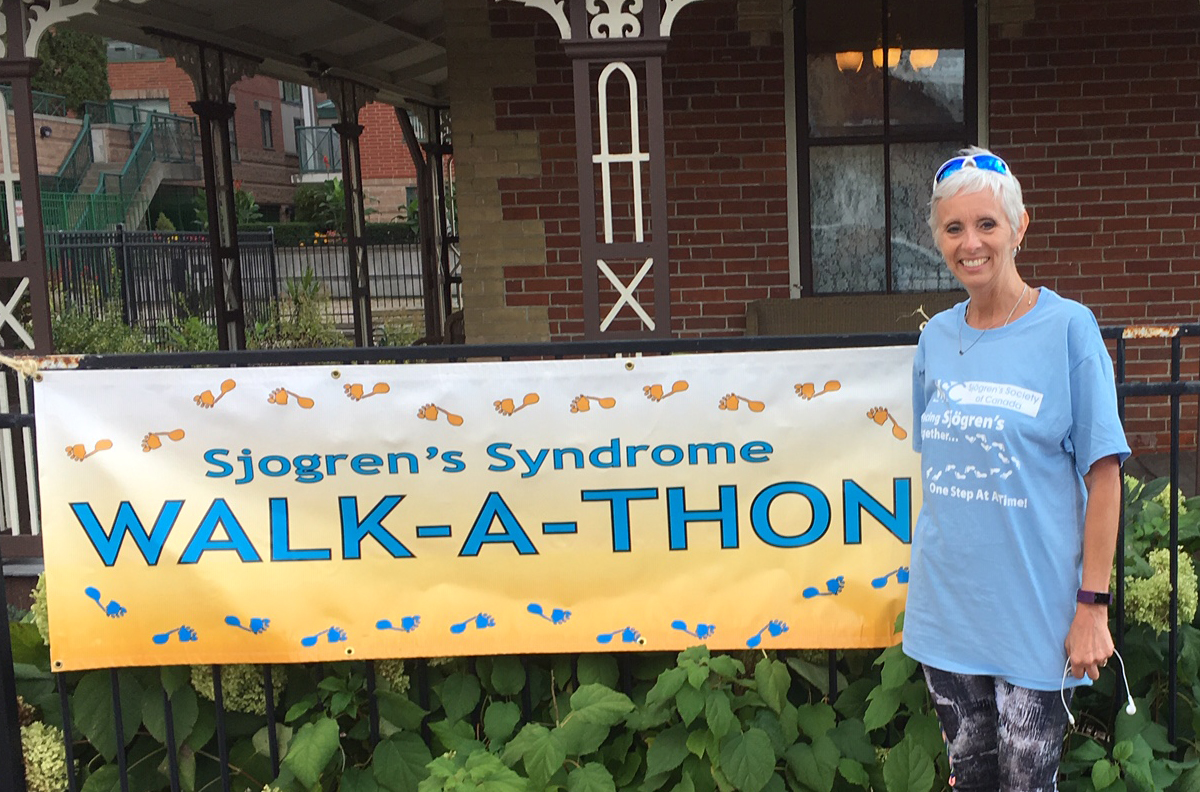 Marilyn Thom standing in front of a Walk-a-Thon banner