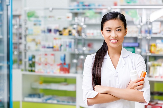 Pharmacist standing with prescription bottles