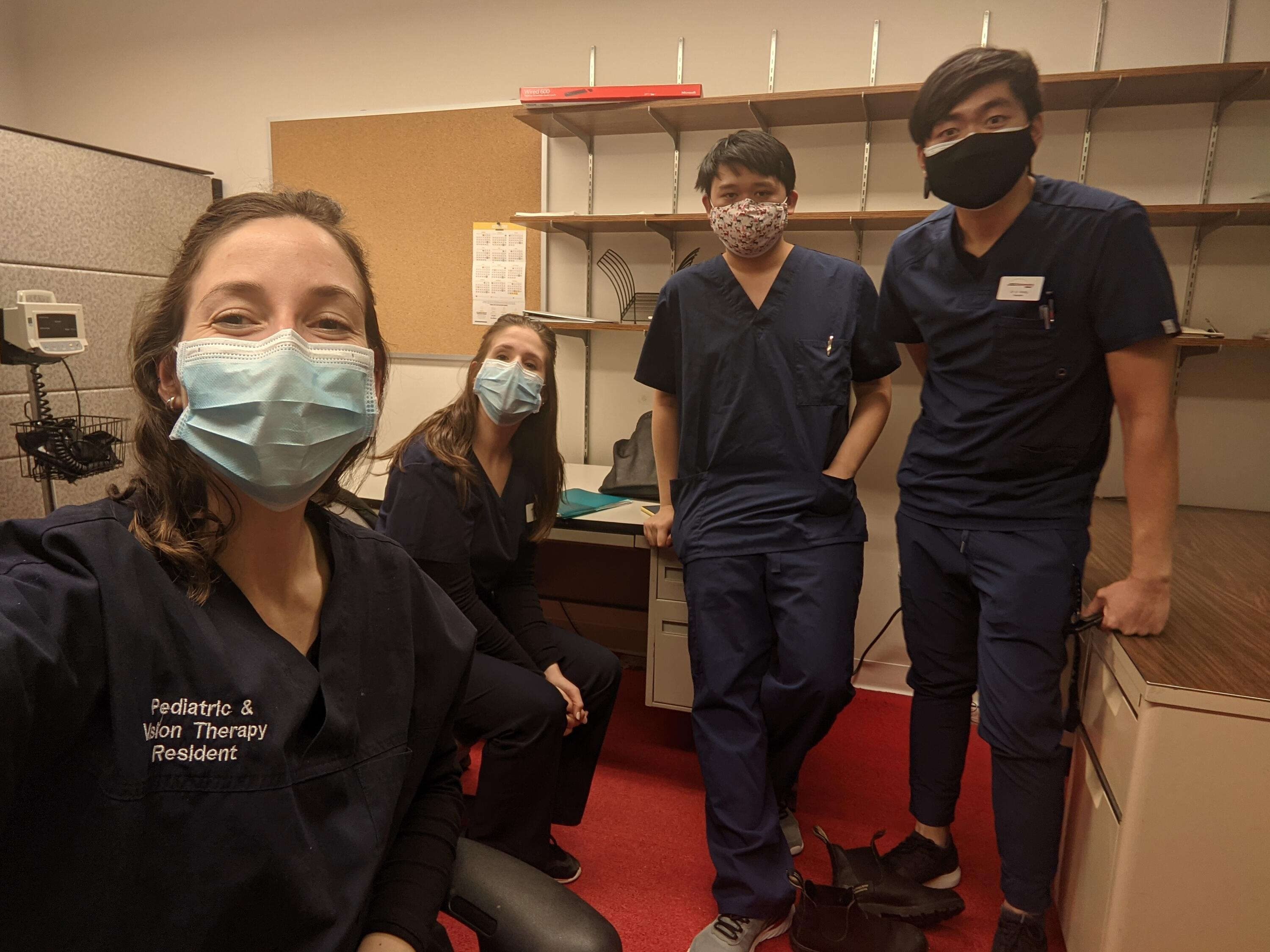 Four optometrists in an exam room - left to right: Dr. Zoe Stein, Dr. Rachel Amaral, Dr. Chen and Dr. Wong