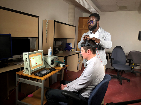 Richard Donkor looks at a computer monitor while adjusting Dr. Ben Thompson's headset