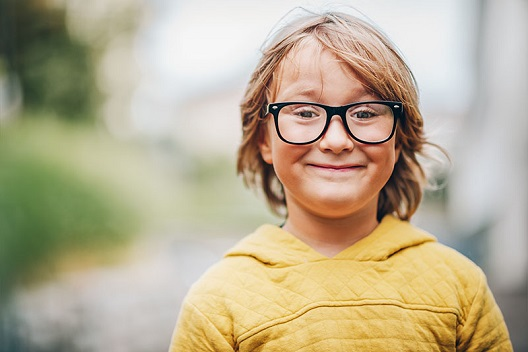 Close-up portrait of a little boy wearing eyeglasses and a yellow sweatshirt