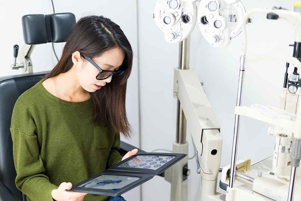 Woman wearing sunglasses looking at a tablet in an optometry exam room