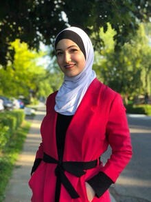 Yara Mohiar, dressed in a white hijab and red coat, stands ona tree-lined street