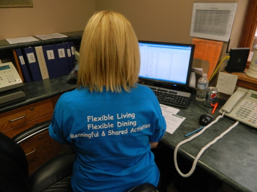 A woman is seated and wearing a t-shirt with the writing 'flexible living flexible dining shared and meaningful activities' written on the back.