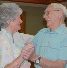 An older couple dances and smiles.