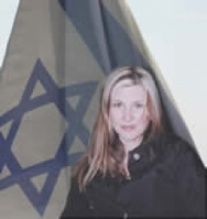 Marianne Popovacki with an Israeli flag behind her.