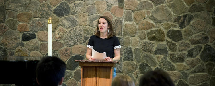 Female student standing at a podium giving a speech