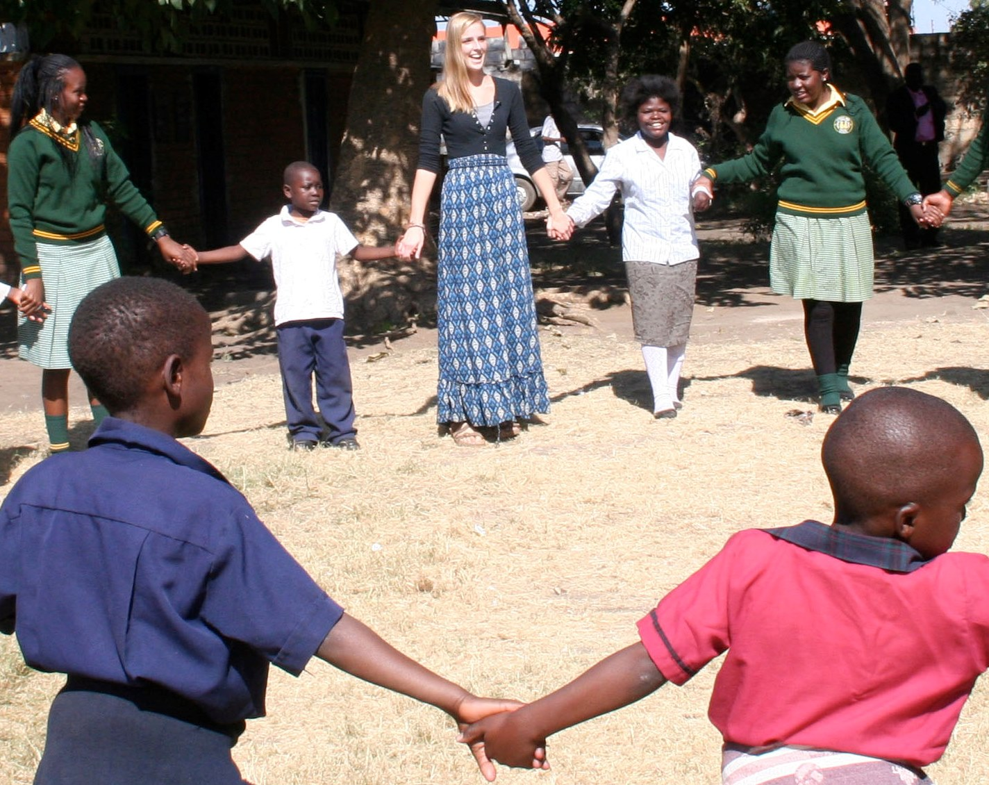 Rachel holding hands with Zambian children in a circle