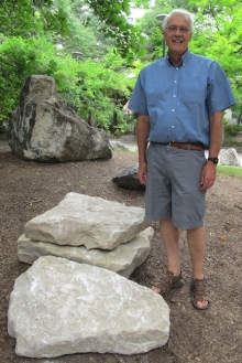 Columbus limestone rock in the Rock Garden with a person standing by it.